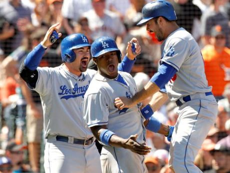 Adrian Gonzalez and Yasiel Puig, both contenders for the National League All-Star Final Vote, celebrate with Andre Ethier after scoring on a double by catcher A.J. Ellis at ATT&T Park.