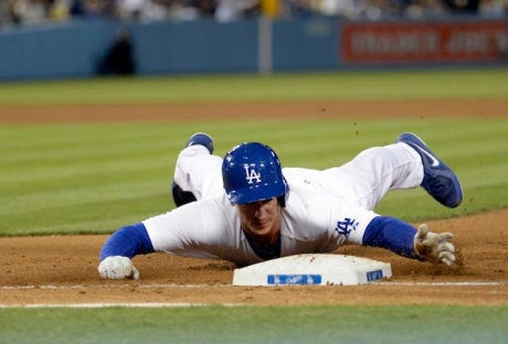 Mark Ellis dives for the bag on a pickoff attempt by the Rockies.