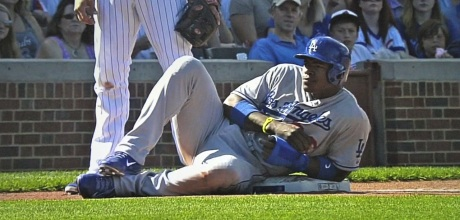 Dodger outfielder Yasiel Puig takes a breather at third base during a game in Chicago.